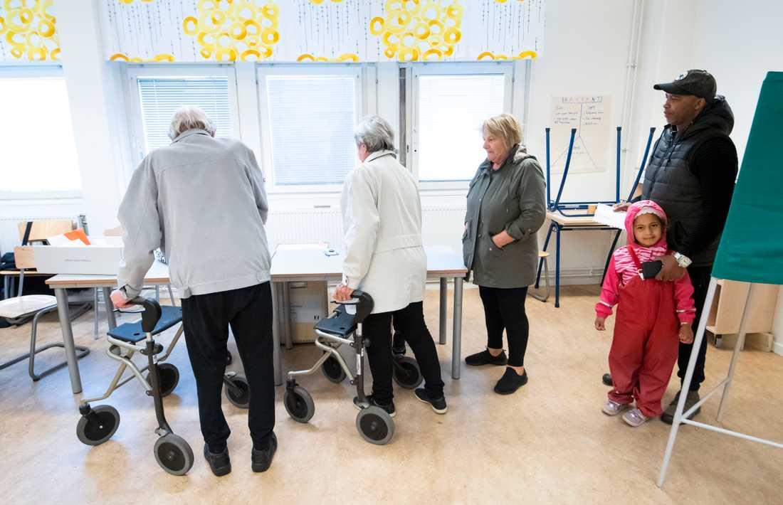 Celia väntar med pappa Hassan Bobo (t h) för att lägga sin röst i vallokalen för Persborg på Värner Rydénskolan i Malmö.