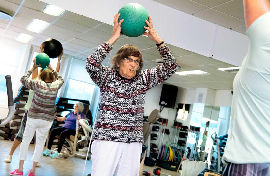 Kerstin Hellgren, 97 år, lyfter upp en medicinboll under cirkelträningen.