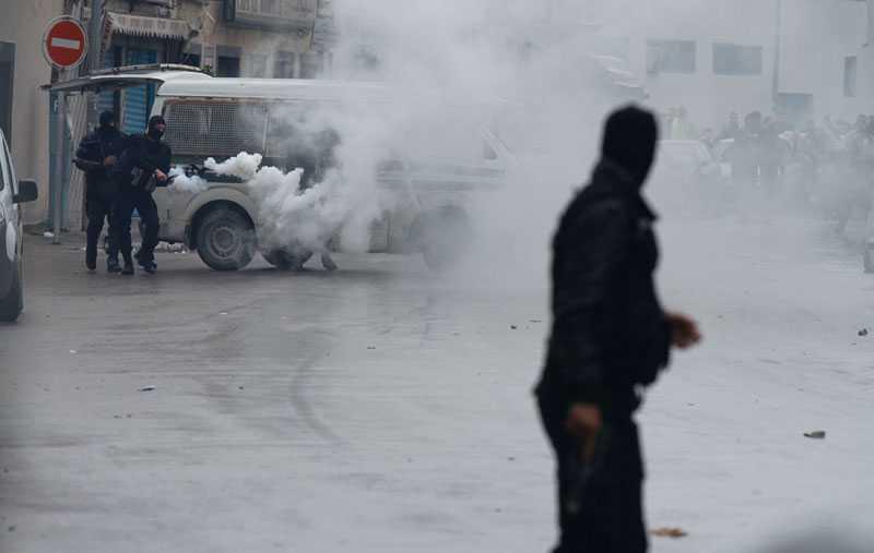 Tårgasen låg tung över Tunis, här avfyrar tunisisk polis ytterligare tårgas mot de tusentals demonstranterna vid inrikesministeriet.