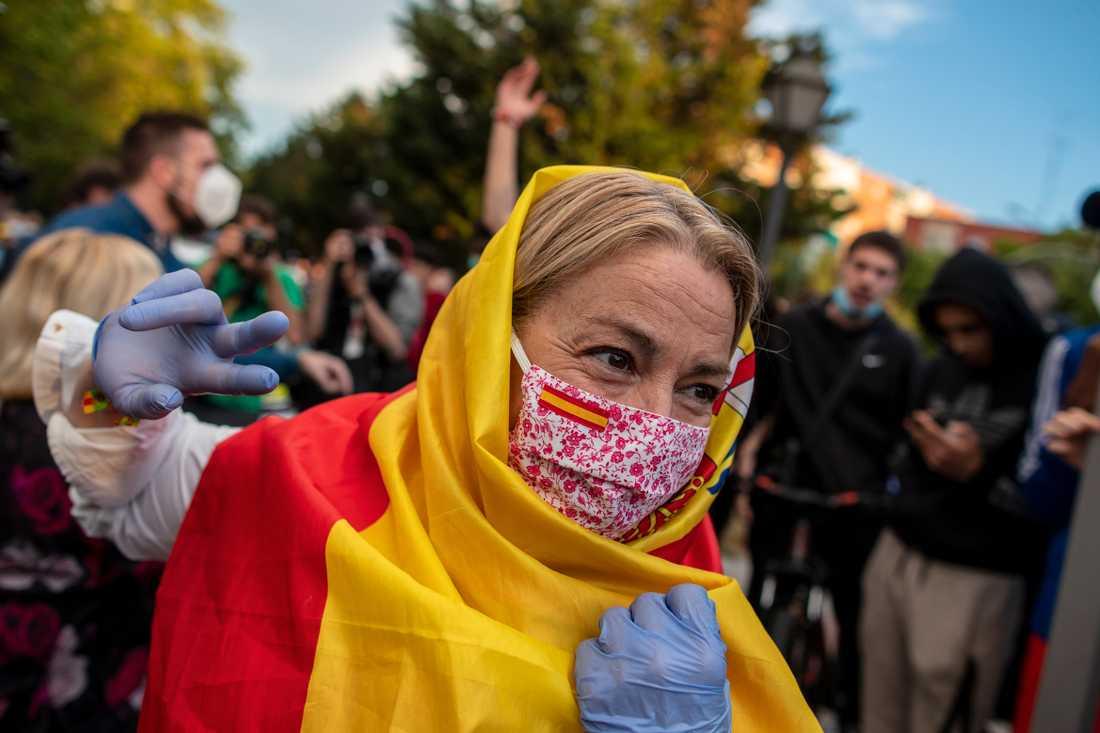 En kvinna draperad i en spansk flagga och med munskydd under en protest mot regeringens hantering av krisen i Alcorcón i tisdags.