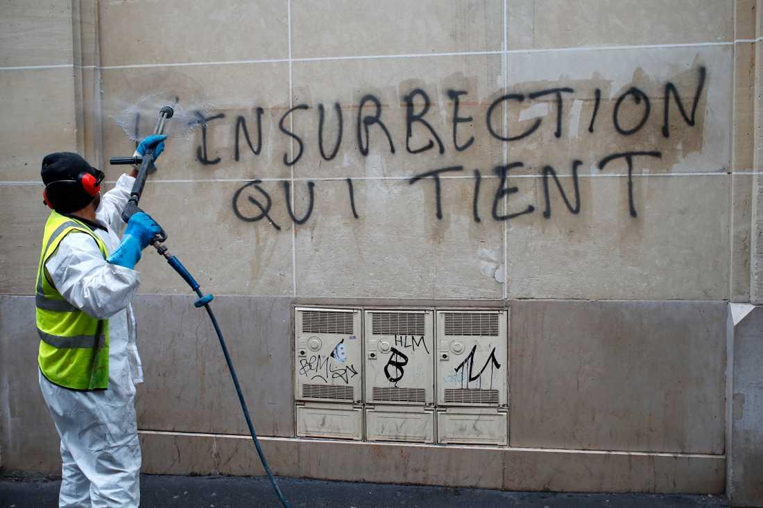 """Graffiti som kan översättas till ungefär """"varaktig revolt"""" städas bort nära Champs-Elysees."""