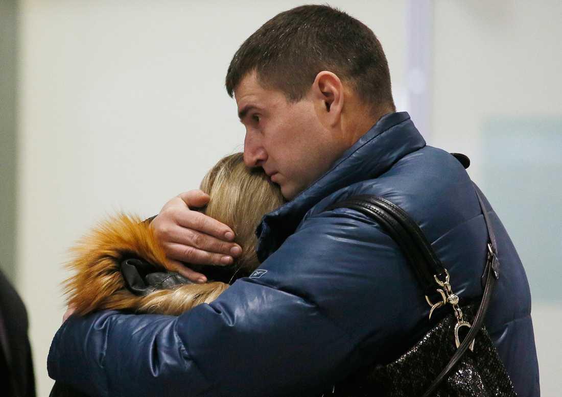 En man kramar om en kvinna på flygplatsen i Sankt Petersburg.
