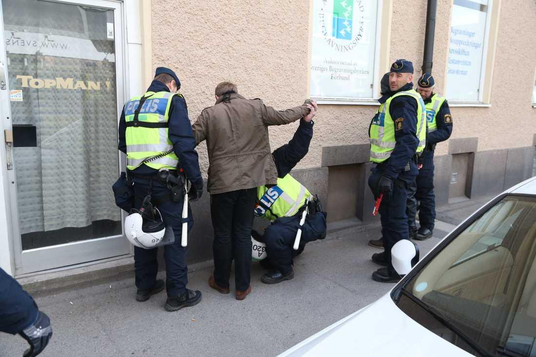 Polis visiterar person inför en demonstration av högerextrema Svenskarnas Parti. Arkivbild.