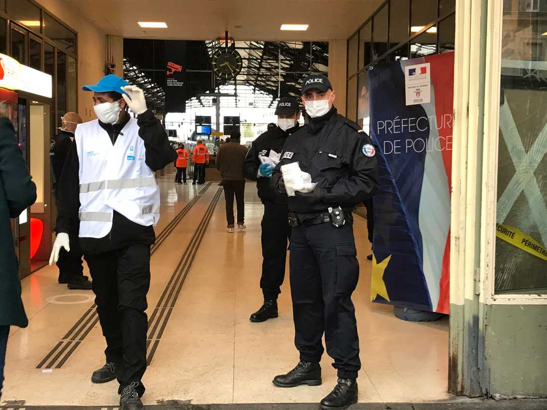 Vid Gare de Lyon, en av den franska huvudstadens fem tågstationer, hjälper poliser till att dela ut munskydd till alla.