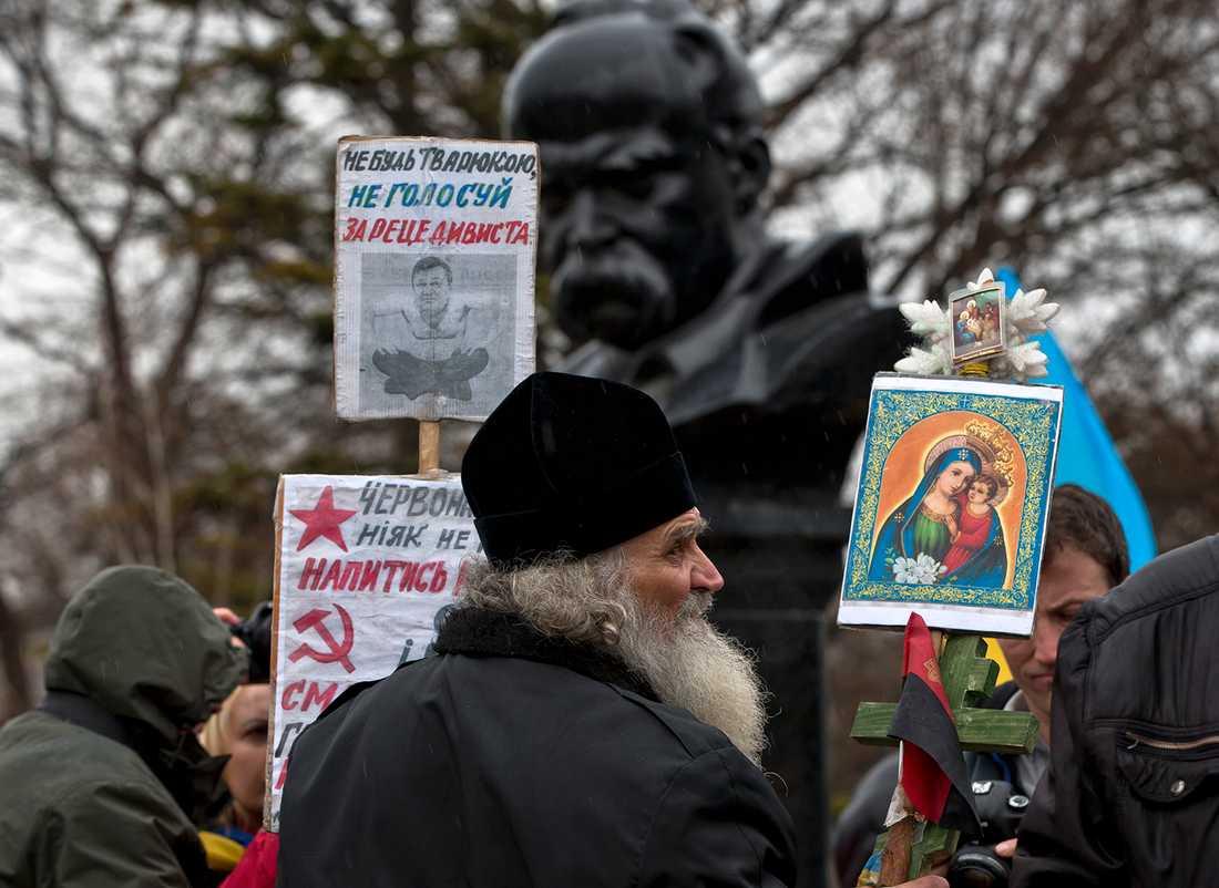 """För Ukraina En ukrainsk-ortodox munk på en demonstration för att Krim ska tillhöra Ukraina i Simferopol fredag 7 mars. På plakatet står bland annat """"Rösta inte för brottslingen"""", """"Röda stjärnan kräver mer blod"""" och """"Hammaren och skäran är död och hunger""""."""