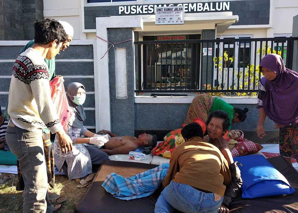 Sjukvårdspersonal behandlar en skadad person utanför ett sjukhus i byn Sembalun Selong.