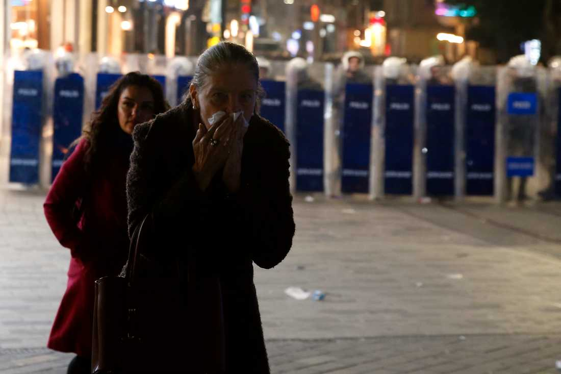 En kvinna håller sig för ansiktet efter att turkisk polis avfyrat tårgas.
