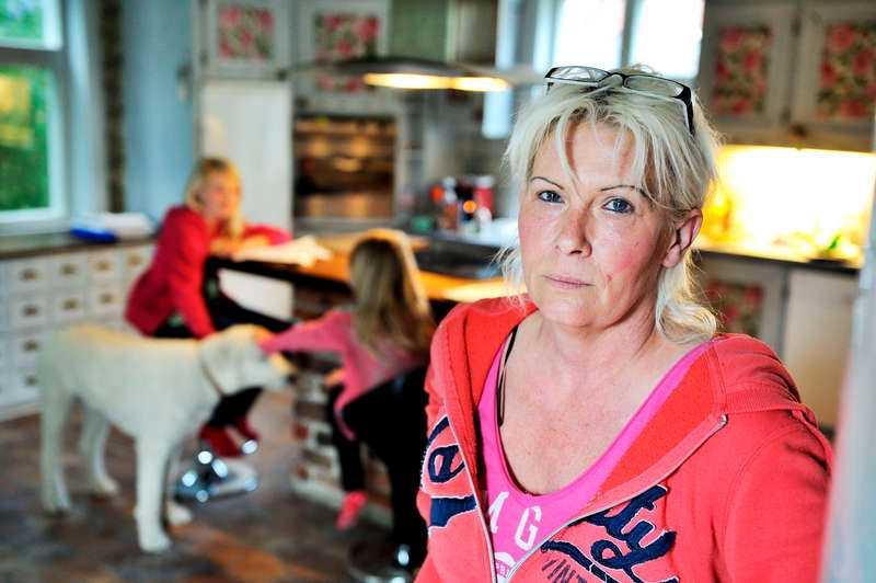 """""""Hela systemet är fel""""  Carina Erlandsson, 50, drabbades av en mördarbakterie – och blev uppsagd från sitt jobb. """"Det finns inget skyddsnät för den som är sjuk"""", säger hon. I bakgrunden sitter döttrarna Ronja och Madicken med hunden Assar."""