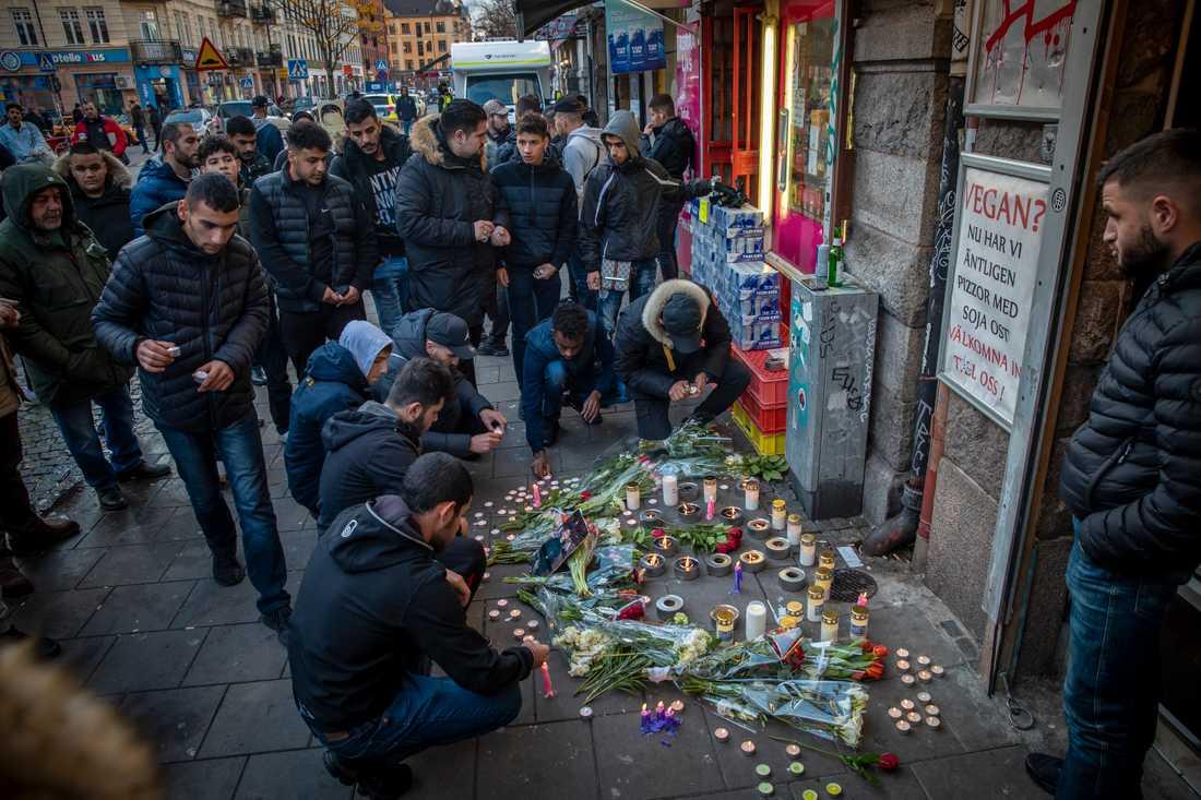 Vänner till de skjutna har samlats utanför pizzerian och tänt ljus och lämnat blommor.