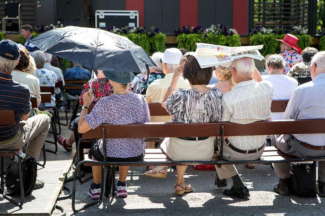 Åskådare tar skydd från värmen under en lunchkonsert i Kungsträdgården.