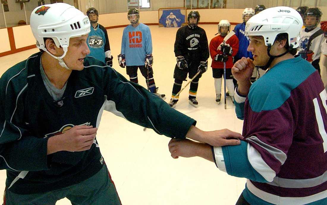 """Derek Boogaard, till vänster, lär här tillsammans med sin bror unga hockeyspelare mellan 12-15 år olika slagsmålstekniker under """"Boogaard Fight Camp."""""""