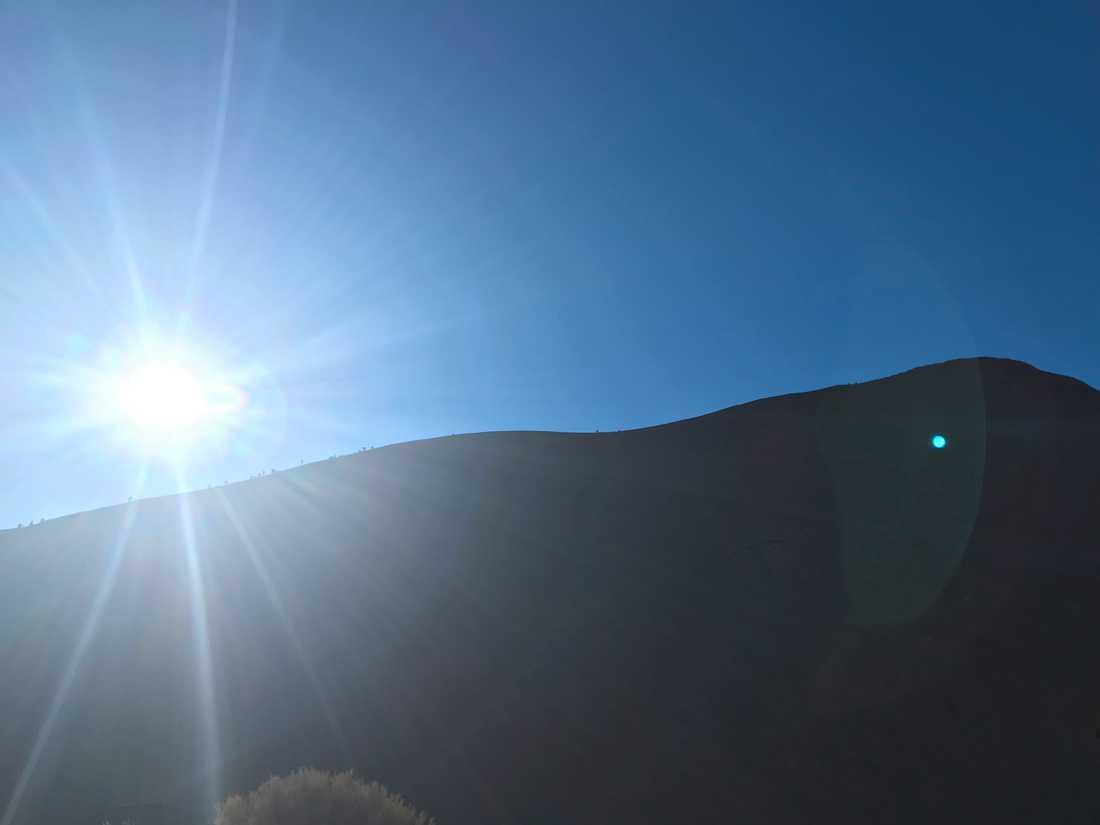 Klättrare på Uluru (Ayers Rock) avtecknar sig som små prickar längs klippans kant.