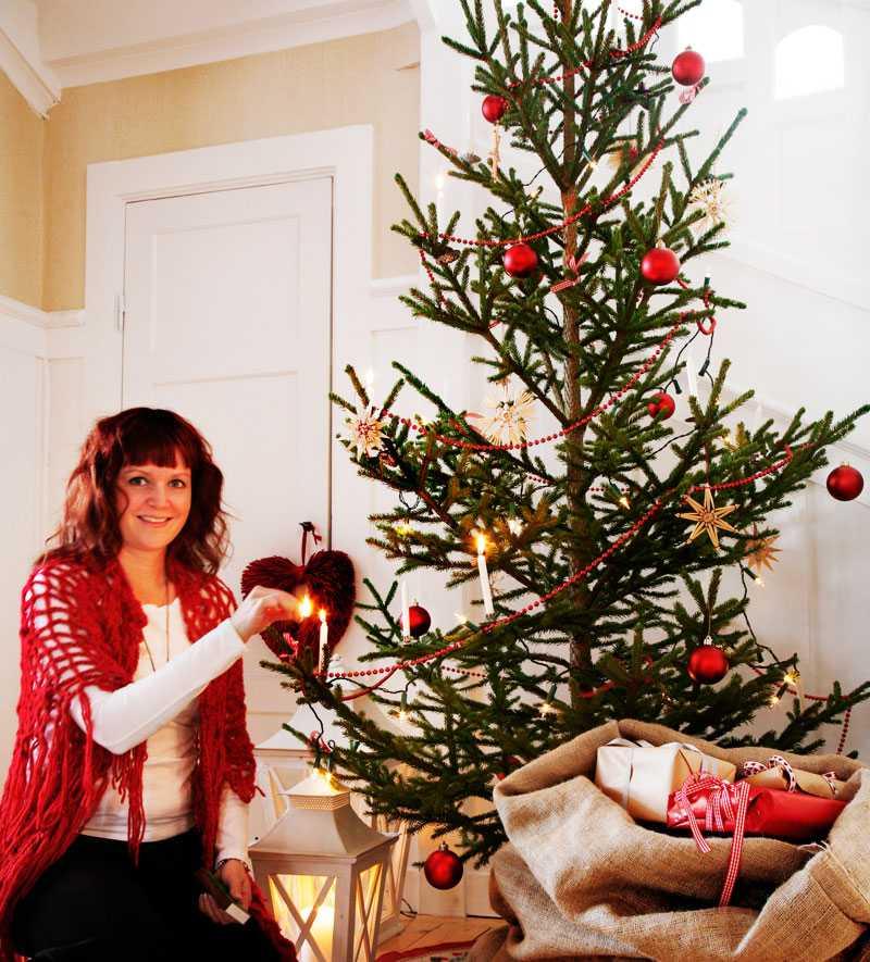 Granen i hallen lyser upp hela trapphuset. Julgransfoten är nerstoppad i en säck av juteväv och ytterligare en säck är fylld av vackra klappar.
