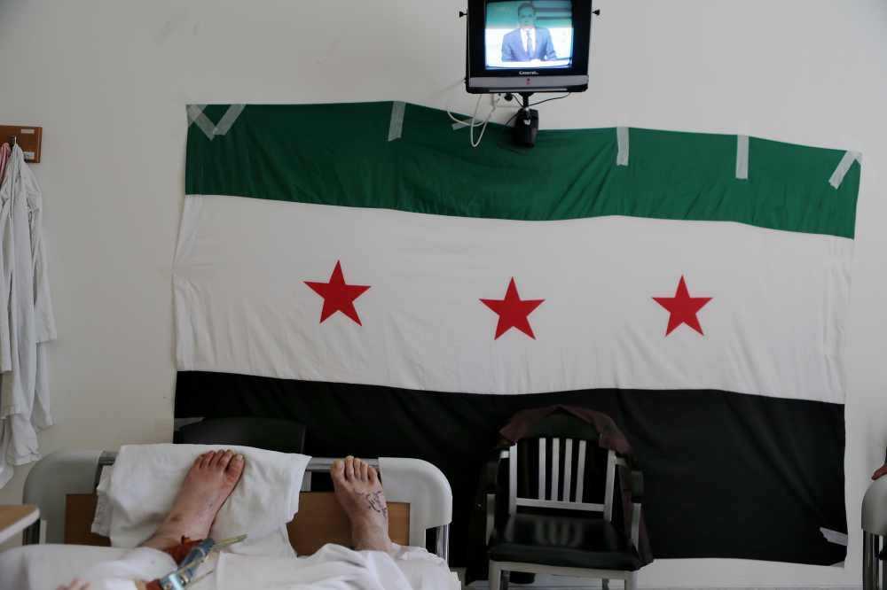 Rebellernas flagga En skadad man fördriver tiden med att titta på TV. Under hänger den syriska flagga som användes under 50- och 60-talen och som nu tagits tillbaka av de syriska frihetskämparna.