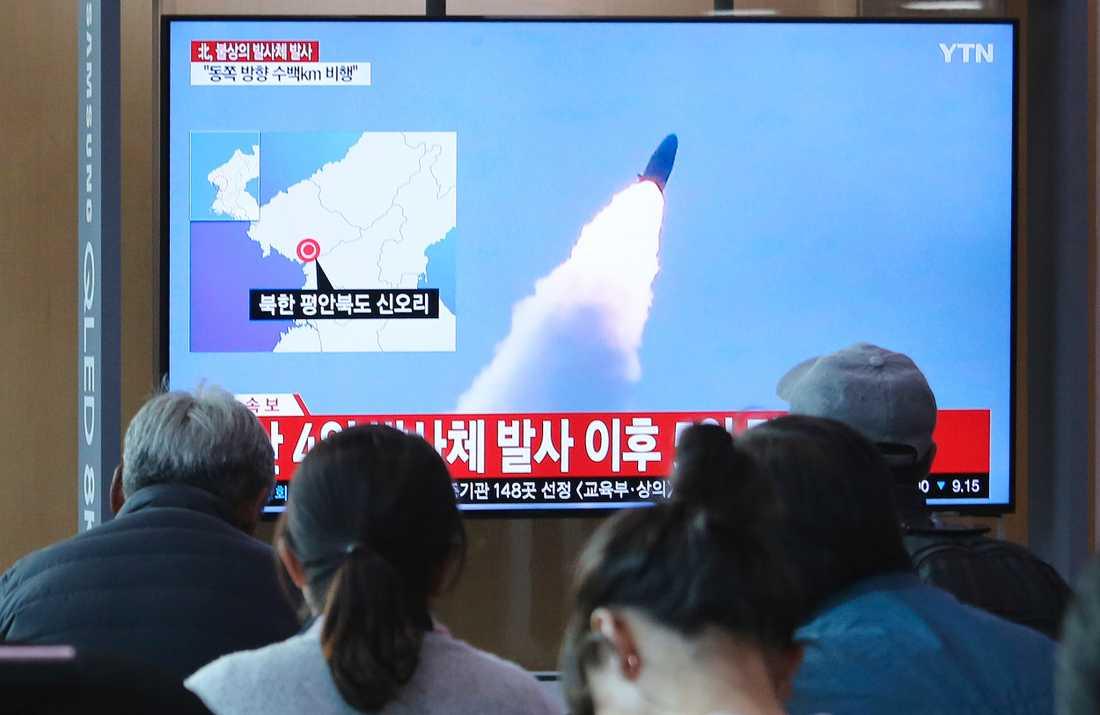 Människor i sydkoreanska Seoul tittar på bilder av ett nordkoreanskt robottest den 9 maj.