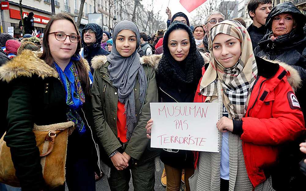 """Över en miljon människor samlades i helgen för att hedra offren i terrorattacken mot satirtidningen Charlie Hebdo. Amen Belmecheri, längst till höger, tillsammans med sina väninnor.  Skylten betyder """" Vi är muslimer, inte terrorister""""."""
