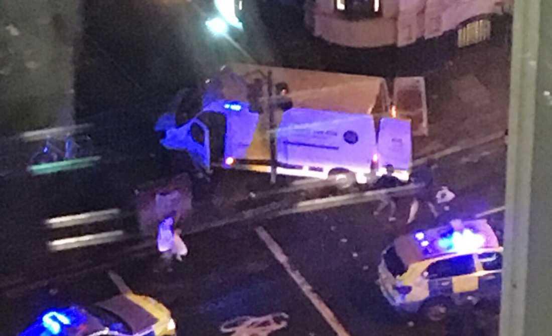 Bilder på sociala medier visar hur en vit skåpbil som kört upp på trottoaren bevakas av polis.