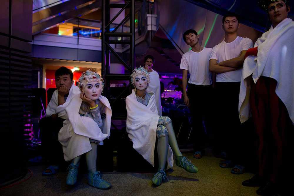 Artister i den världsberömda uppsättningen Cirque du Soleil tar en paus bakom scenen under en gala i ett shoppingcenter i Peking, Kina.