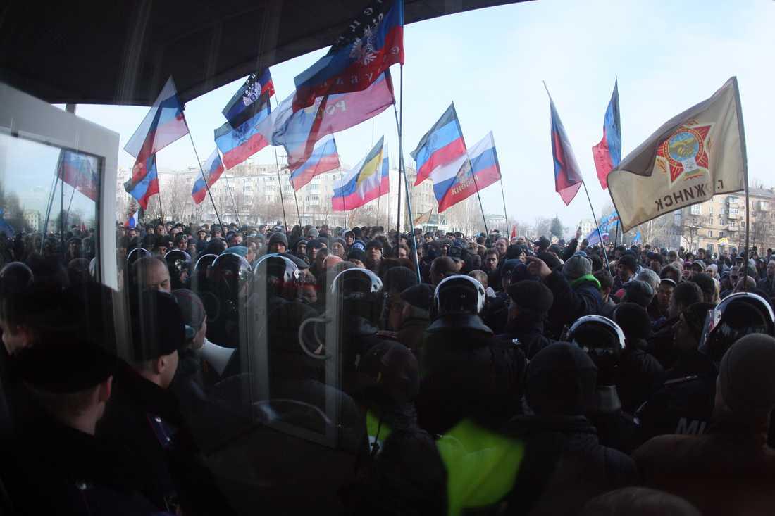 En mur av poliser vaktar en byggnad i ukrainska staden Donesk under en pro-rysk demonstration.