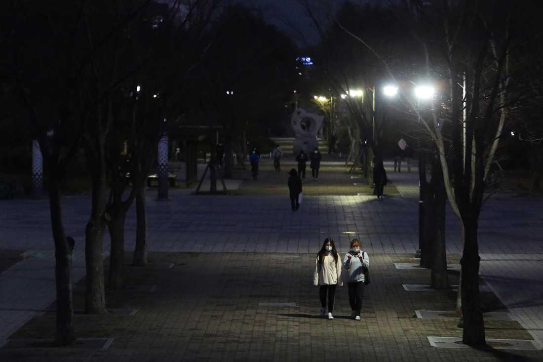 Två personer med munskydd på promenad längs en gata i Goyang, nordväst om Seoul, under söndagen.