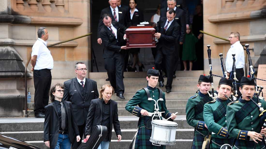 Kistan med Malcolm Young bärs ut ur kyrkan. I täten går Angus Young med broderns gitarr i handen.