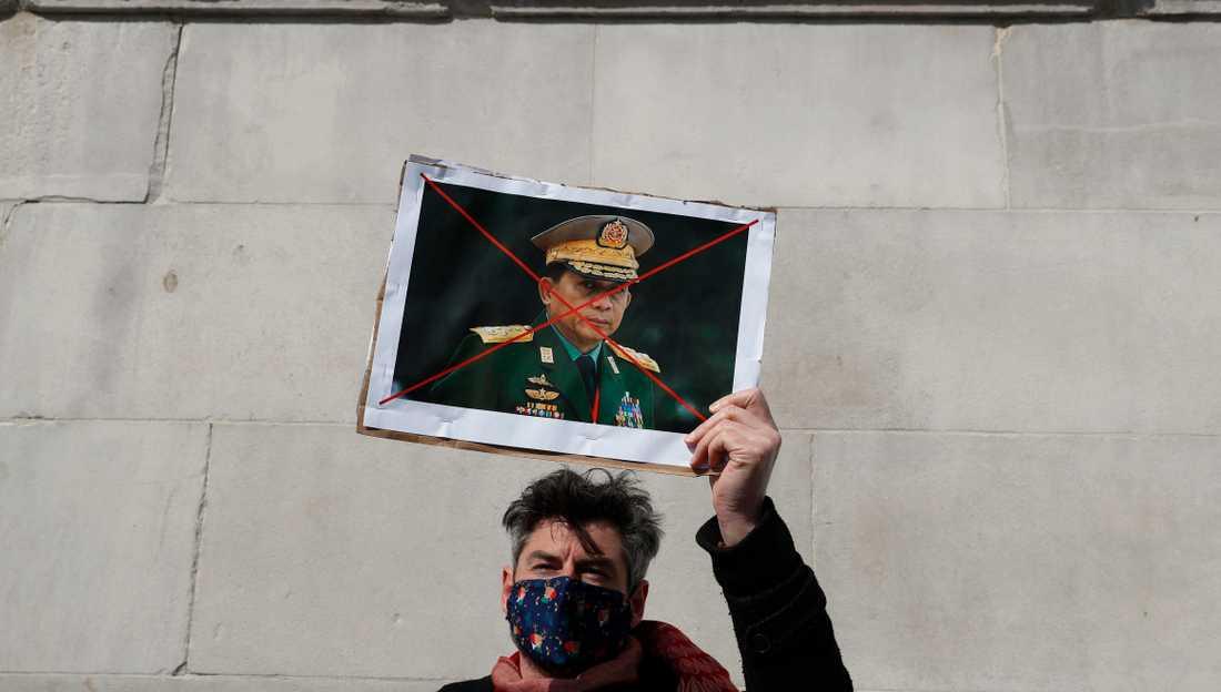 En anhängare till avsatta Aung San Suu Kyi håller upp en bild på en överkryssad Aung Hlaing, juntaledaren som tog makten i Myanmar den 1 februari.