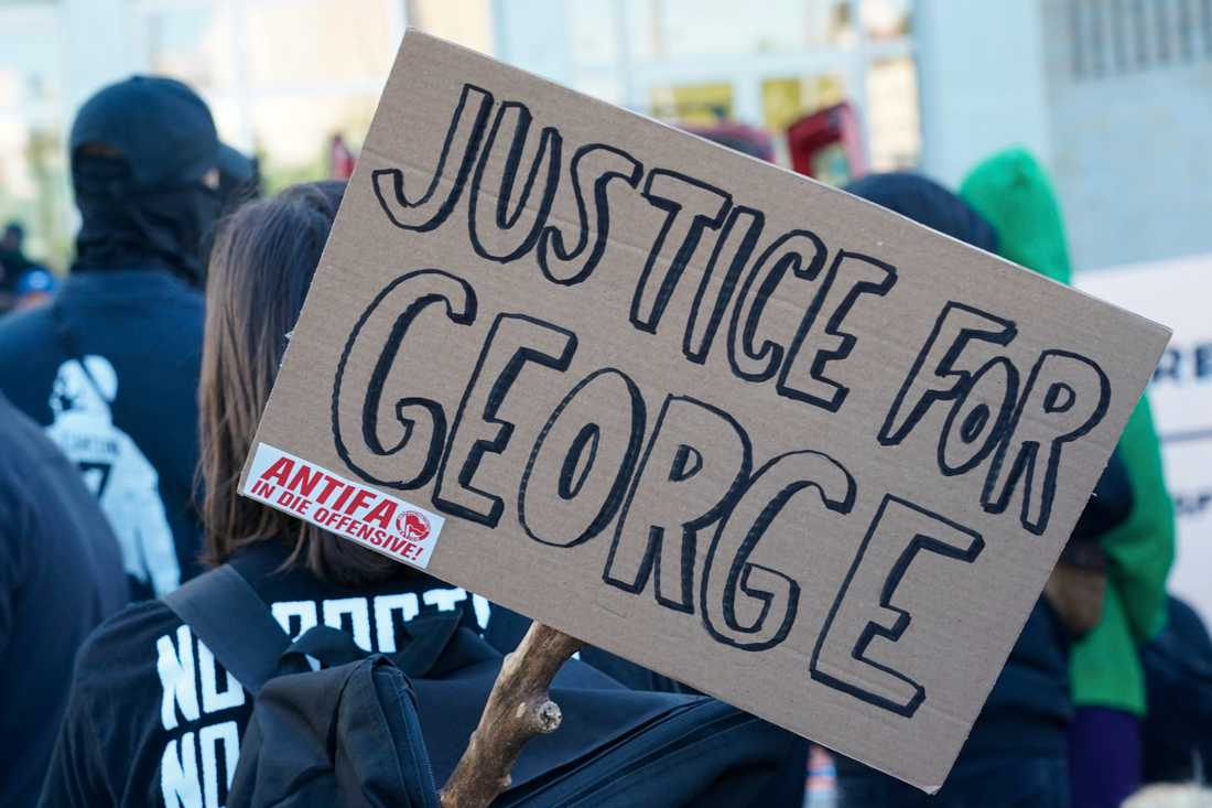 """En skylt med texten """"Rättvisa för George"""" (som syftar på George Floyd som dödades i ett brutalt polisingripande) och ett klistermärke med texten """"Antifa på offensiven"""" vid en tysk demonstration mot polisvåldet i USA."""