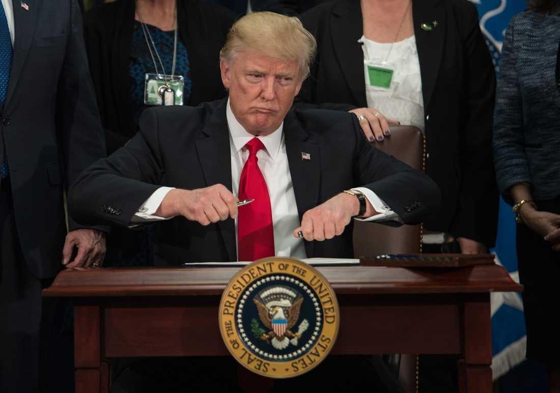 Donald skriver på ordern om muren mot Mexiko.