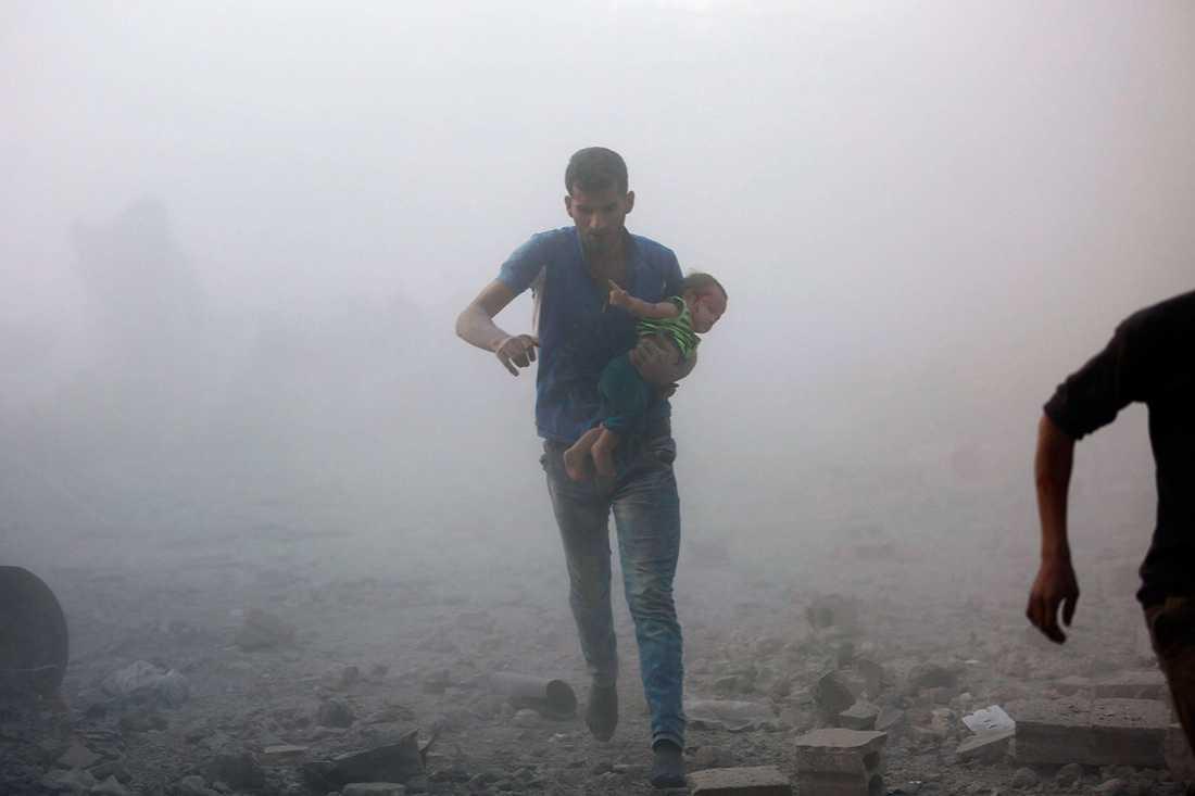 En man springer mot skydd i Kafr Batna efter luftangrepp.