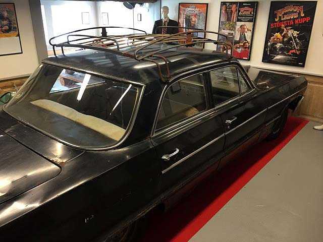 Jönssonligans klassiska bil, en Chevrolet Impala från 1964 står i ett privat garage. Massvis med fans vill lägga vantarna på den, men bilen är inte till salu.