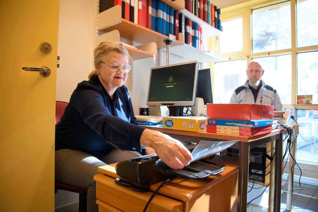 Genom laminering kan overheadbladen bli till ansiktsvisir som kan spritas och användas igen. På bilden rektor Monica Nygren och vaktmästare Mats Olsson som kom på idén tillsammans.