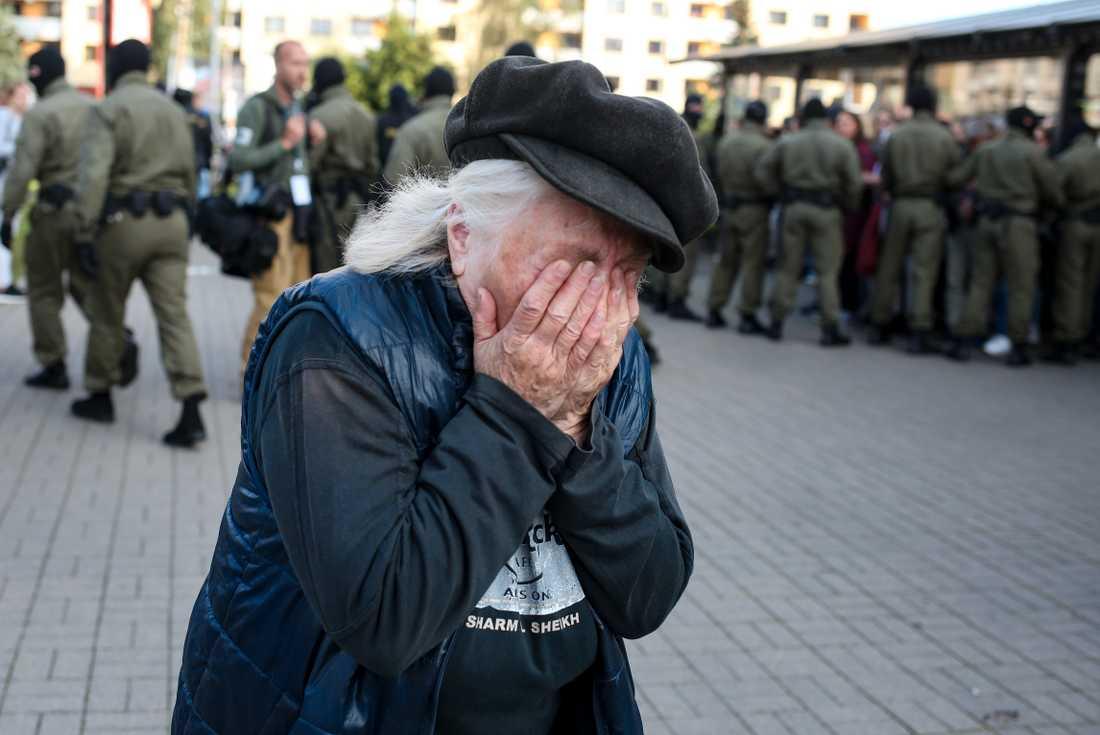 En äldre kvinna reagerar på polisens bortföranden av demonstranter under lördagens protester i Minsk, Belarus.