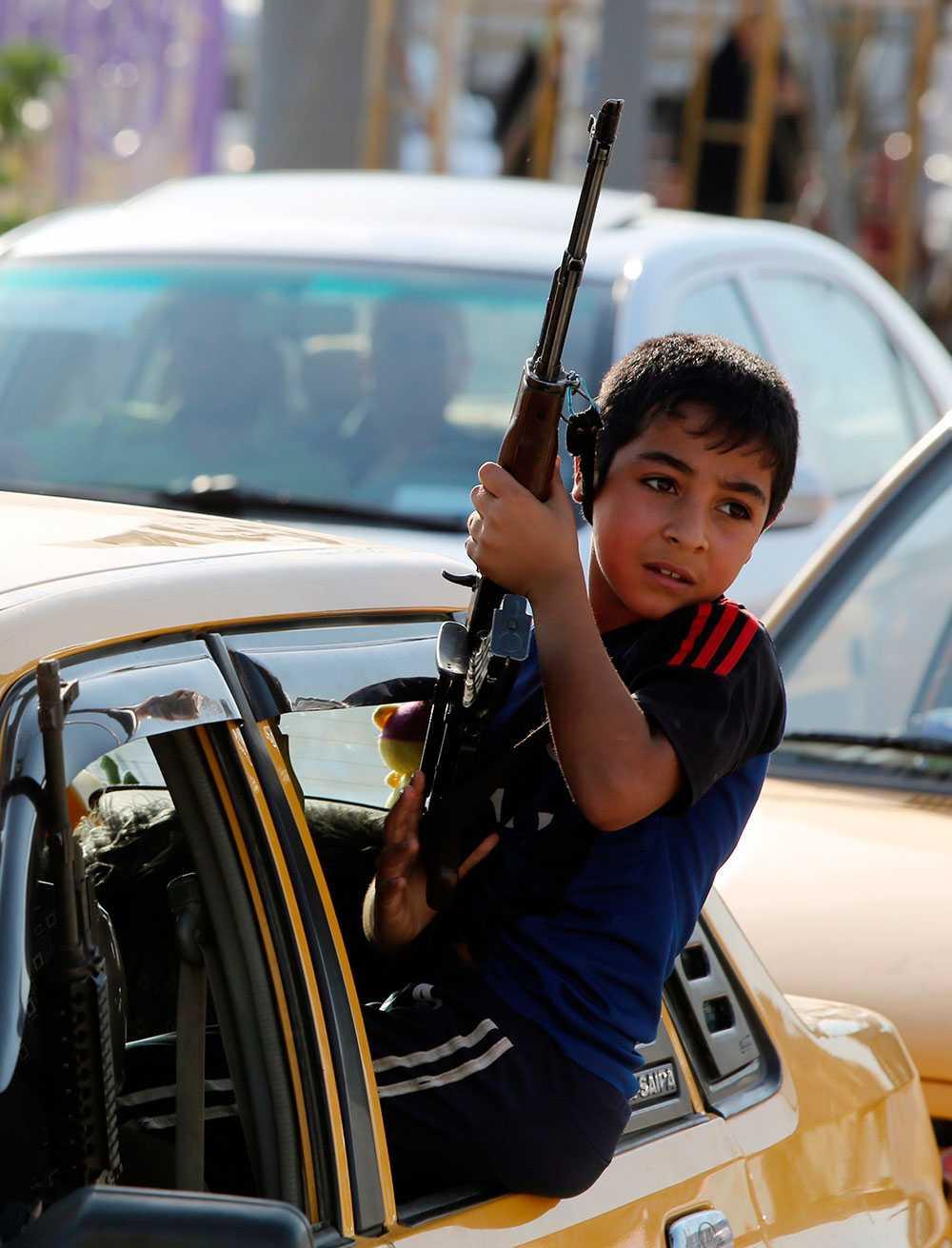 En beväpnad pojke på väg för att ansluta sig till Iraks säkerhetsstyrkor.