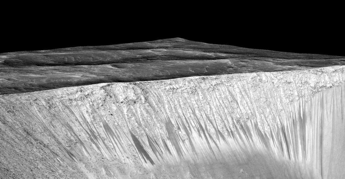 Mörka stråk längs sluttningen av kratern Garni på Mars. Stråken, som är några hundra meter långa, består av saltlösningar som bildas när vatten rann längs sluttningen.