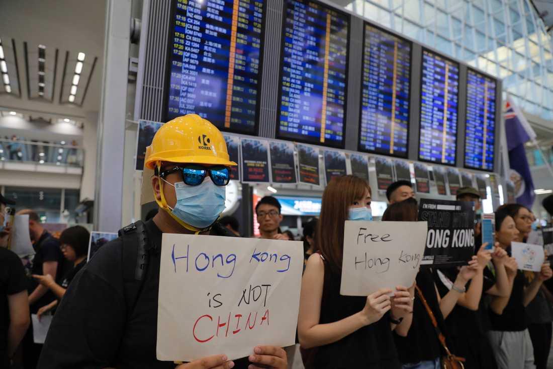 Demonstranter välkomnar människor som anländer till Hongkongs flygplats.