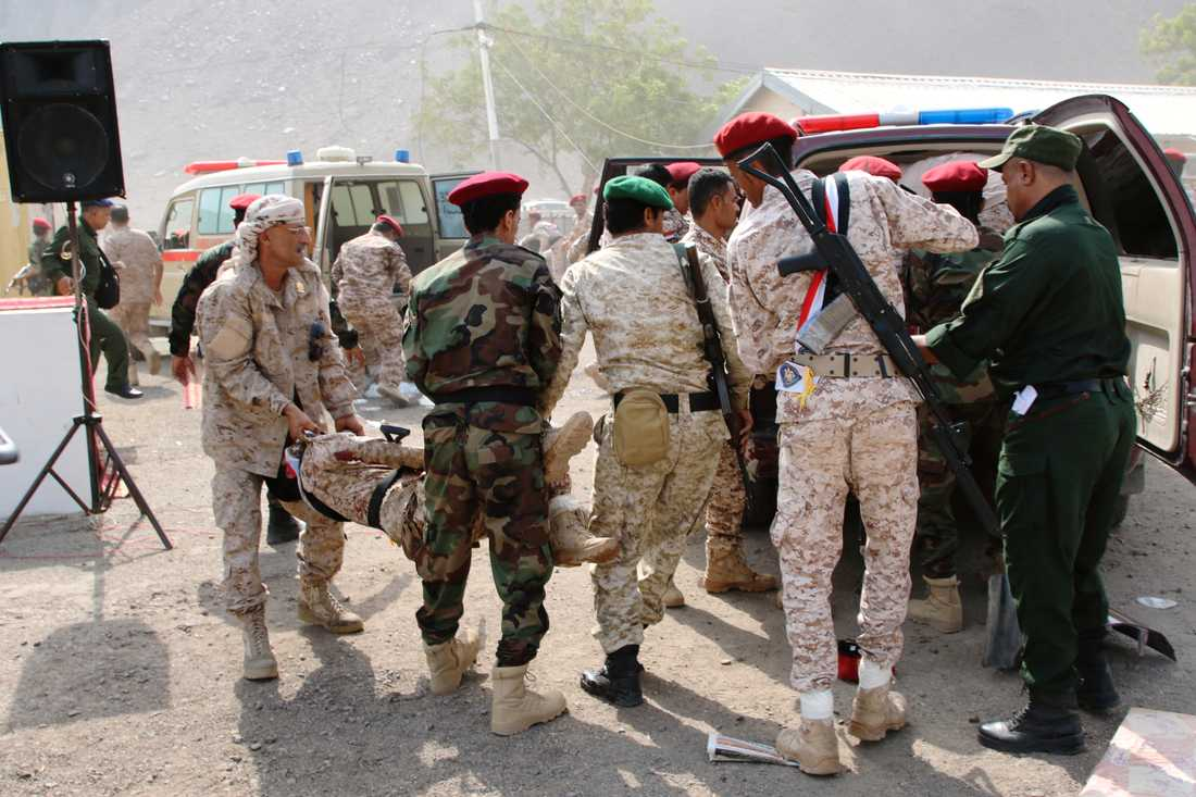 Soldater hjälper en skadad kollega efter attacken mot en militärparad i Aden, Jemen.