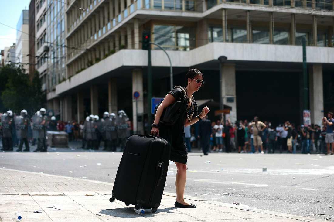 En turist korsar gatan just som demonstranter och polis drabbar samman.