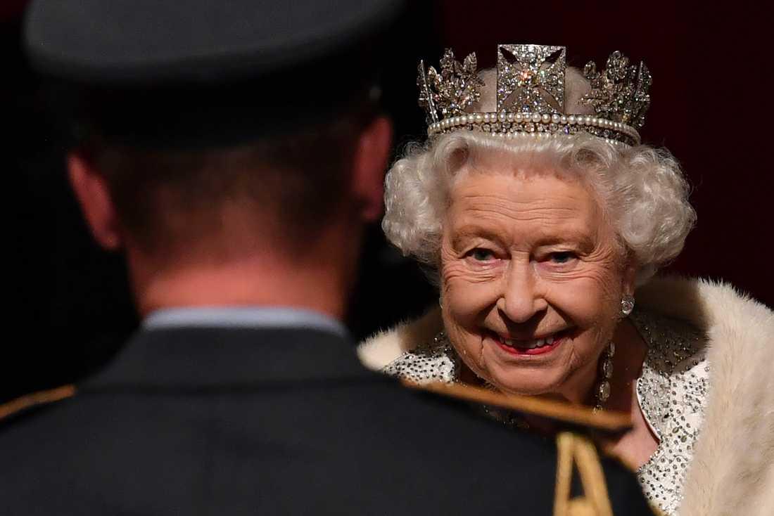 Storbritanniens drottning Elizabeth i samband med den senaste statsöppningsceremonin, den 14 oktober. Då i diadem – nu i hatt.