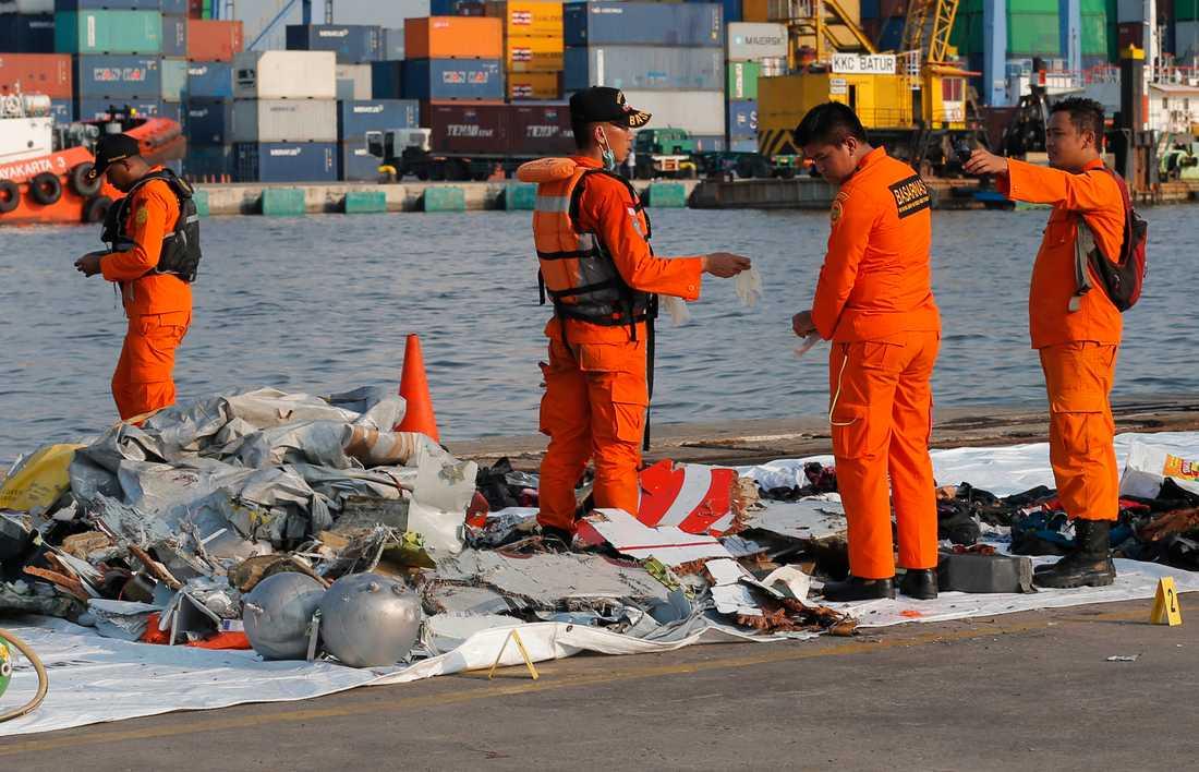 Indonesisk sökpersonal undersöker föremål i närheten av platsen där det indonesiska passagerarflygplanet störtat.
