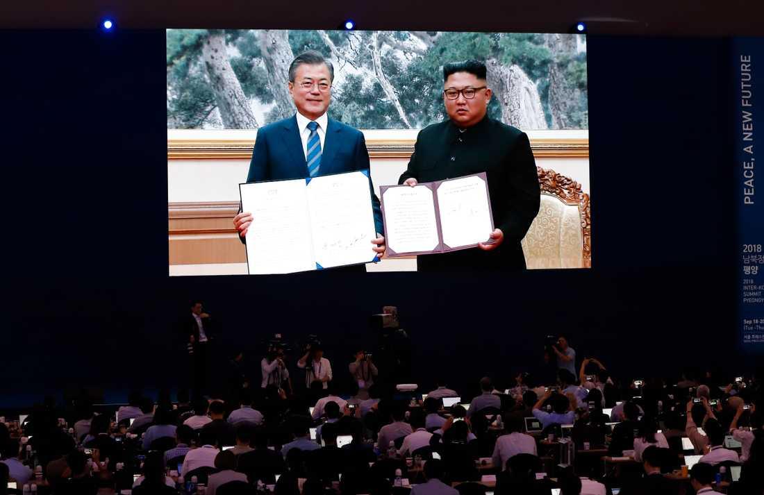 Journalister tittar på en stor skärm när Sydkoreas president Moon Jae-In och Nordkoreas diktator Kim Jong-Un visar upp undertecknade dokument efter onsdagens överläggningar.