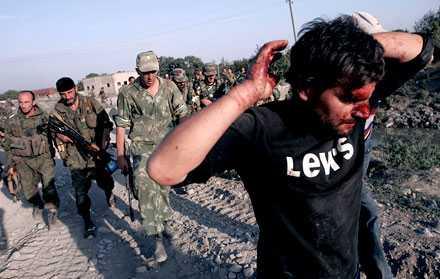 En skadad civilklädd georgisk man förs fram som krigsfånge av ryska soldater i byn Zemo Nikozi, 15 kilometer från sydossetiska huvudstaden Tshinvali.