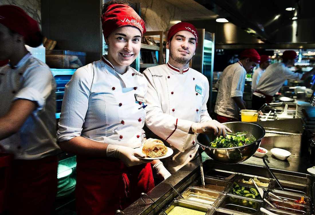 """Felicia Carstens, 19, och Timothy Carmona, 21, jobbar på Vapiano Kungsbron i Stockholm, och får lön enligt kollektivavtal. """"När jag kom till Stockholm var det viktigt att få ett jobb, sen började föräldrar och andra säga att det var viktigt med kollektivavtal. Jag har inte tänkt så mycket på att killar tjänar mer än tjejer, eftersom vi har kollektivavtal här"""", säger Felicia. """"Jag tjänar mer här, än jag gjorde på mitt förra jobb. Jag vet faktiskt inte varför killar tjänar mer än tjejer, det kan ju bero på utbildning eller på arbetsgivaren"""", säger Timothy."""