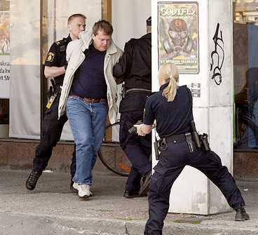 """2. Polisen bakom pelaren sänker sitt vapen och avvaktar. """"Bankpersonalen mår inte bra men har inga skador"""", säger kommissarie Britt Hermansson på krimjouren."""