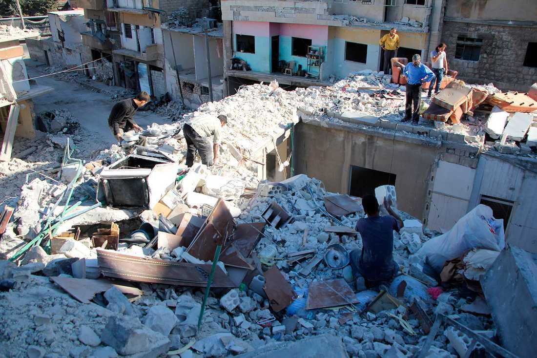 Familjen rensar upp i resterna av det som var deras hus.