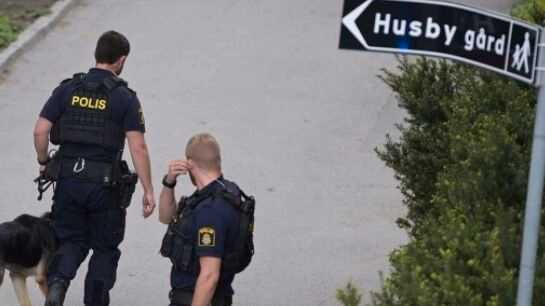 Poliser på plats i Husby efter mordet.