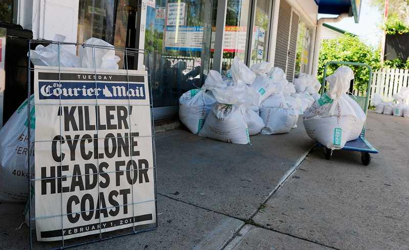 """""""Dödscyklon mot kusten"""" Courier Mails löpsedel utanför en butik i Townsville varnar boende för cyklonen som slår till på onsdag. Mängder av sandsäckar står utanför butiken för att säkra mot den hotande översvämningen som kommer med ovädret."""