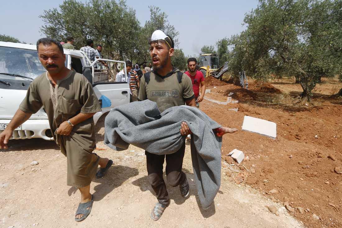 En man bär en död kropp efter flygkraschen i staden Ariha i Syrien.