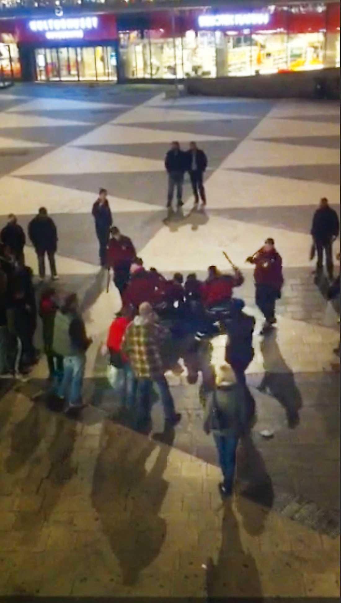 SLÅR MED BATONG Ordningsvakterna öser enligt vittnen slag med batong mot den liggande hemlösa 45-åringen de just kört ut från tunnelbanan. Misshandeln sker mitt i vimlet på Sergels torg.