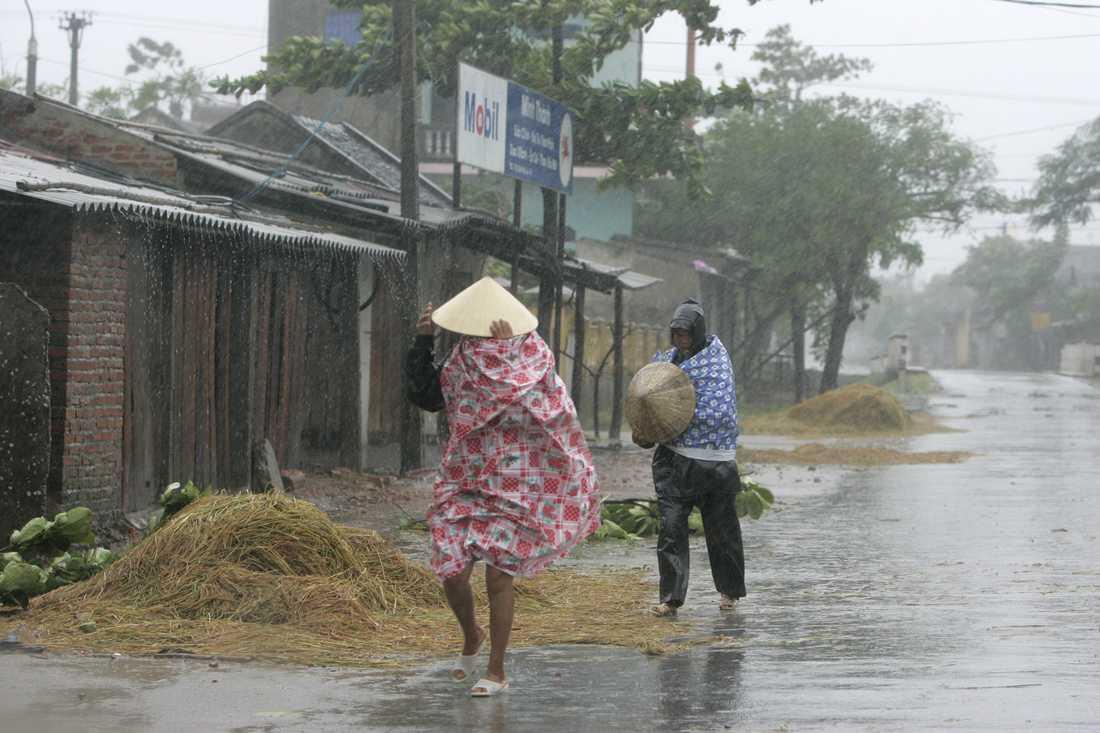 Två kvinnor promenerar i kraftigt regn under en tidigare storm i Vietnam. Arkivbild.