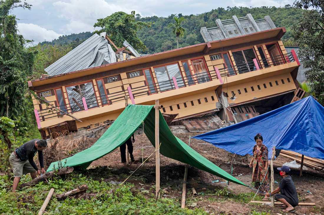 Invånare i Mamuju som förlorat sina hem i skalvet sätter upp provisoriska tält.